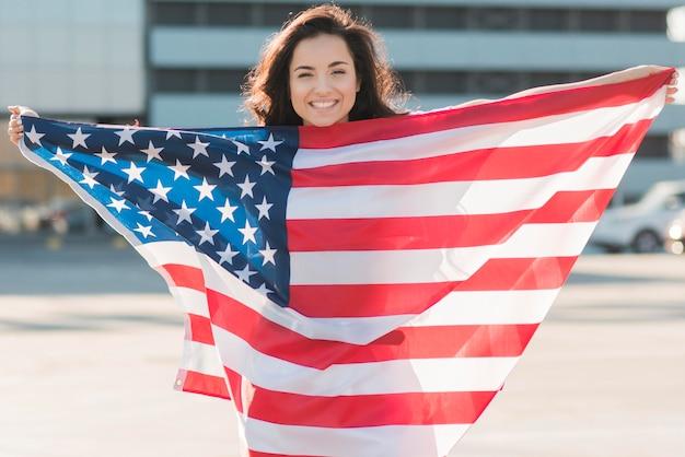 Donna sorridente che tiene la grande bandiera degli sua sopra se stessa