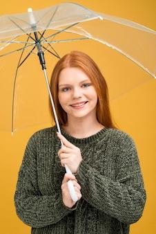 Donna sorridente che tiene ombrello trasparente