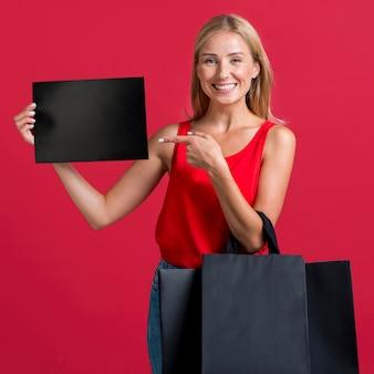Donna sorridente che tiene segno in bianco e molti sacchetti della spesa