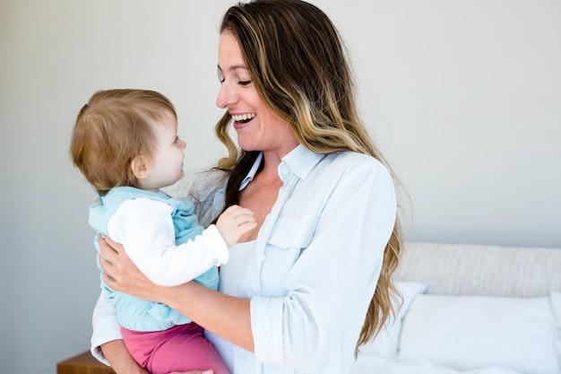 Donna sorridente che tiene un bambino adorabile in una camera da letto