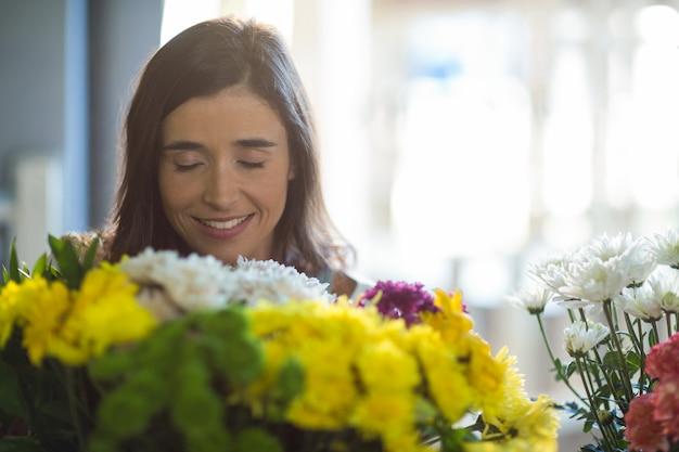 Donna sorridente che tiene un mazzo con gli occhi chiusi nel negozio di fiori