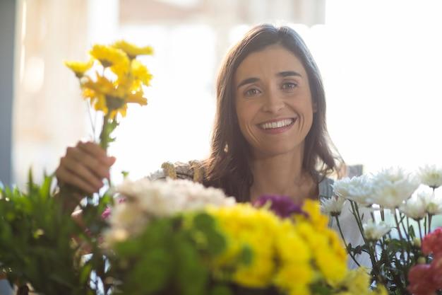 Donna sorridente che tiene un mazzo di fiori al negozio di fiori
