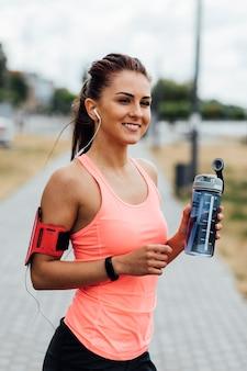 Donna sorridente che tiene una bottiglia di acqua