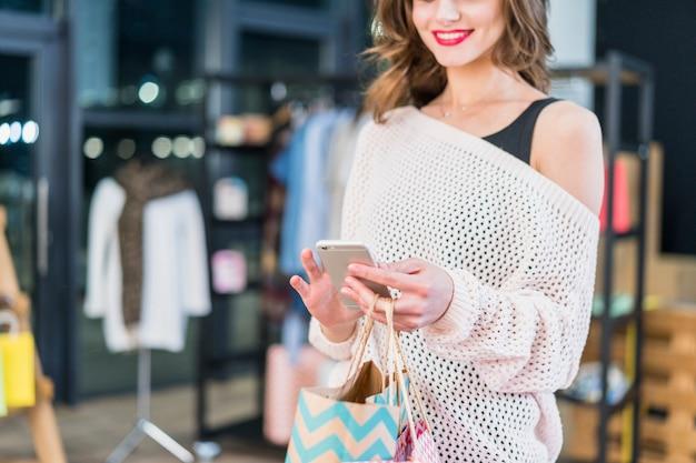Donna sorridente che utilizza smartphone che sta nella sala d'esposizione