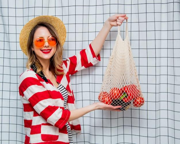 Donna sorridente con cappello e giacca a righe con sacchetto di rete