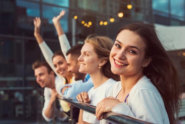 Donna sorridente con gli amici nella priorità bassa