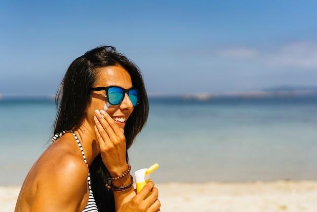 Donna sorridente con gli occhiali da sole che applicano la crema di protezione del sole sul suo fronte nella spiaggia