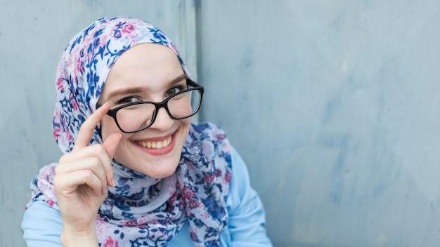 Donna sorridente con gli occhiali e l'hijab