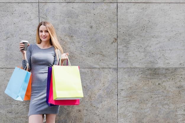 Donna sorridente con i sacchetti della spesa variopinti davanti alla parete
