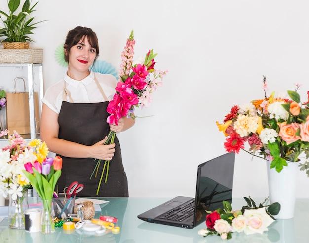 Donna sorridente con il mazzo di fiori che stanno nel negozio floreale