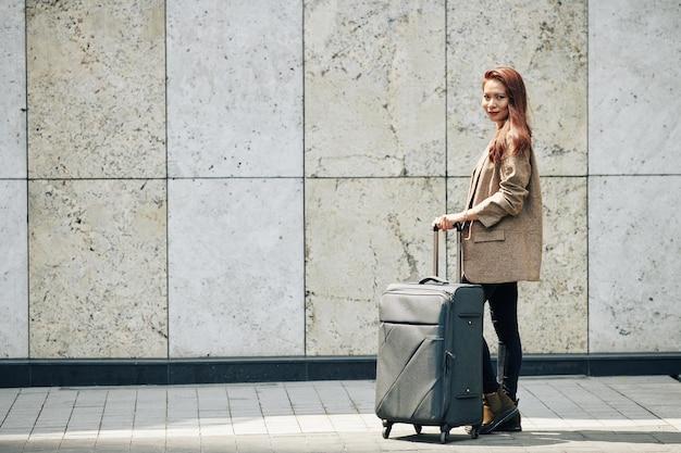 Donna sorridente con la valigia