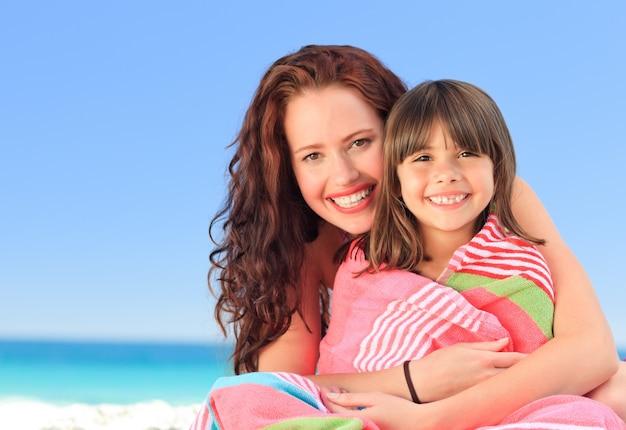Donna sorridente con sua figlia in un asciugamano