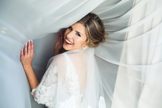 Donna sorridente con tende bianche