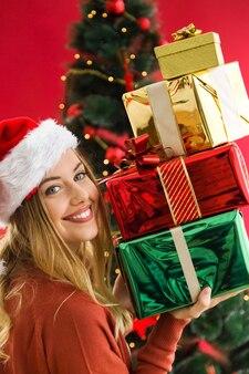 Donna sorridente con una montagna di doni colorati nelle sue mani