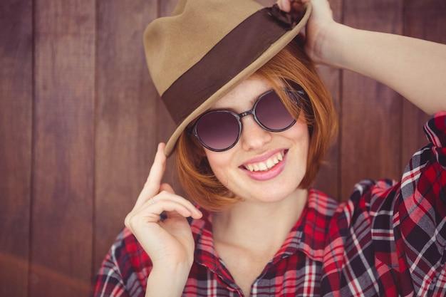 Donna sorridente dei pantaloni a vita bassa che indossa un trilby e gli occhiali da sole