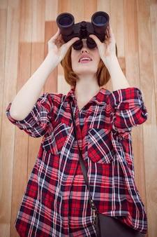 Donna sorridente dei pantaloni a vita bassa che osserva tramite il binocolo