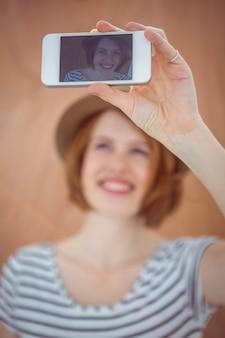Donna sorridente dei pantaloni a vita bassa che prende un selfie