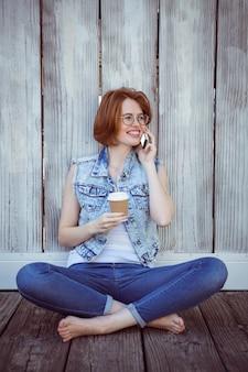Donna sorridente dei pantaloni a vita bassa che si siede al telefono e che tiene un caffè