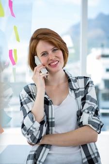 Donna sorridente dei pantaloni a vita bassa che sta nel suo ufficio che fa una telefonata