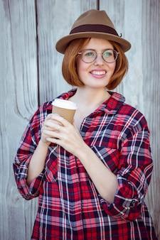 Donna sorridente dei pantaloni a vita bassa che tiene una tazza di caffè