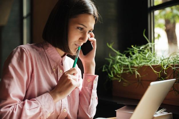 Donna sorridente del brunette che si siede dalla tabella in caffè
