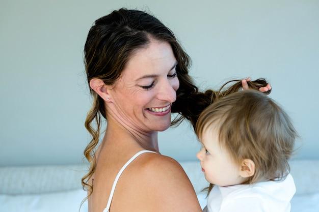 Donna sorridente del brunette che tiene un bambino sveglio che sta giocando con i suoi capelli