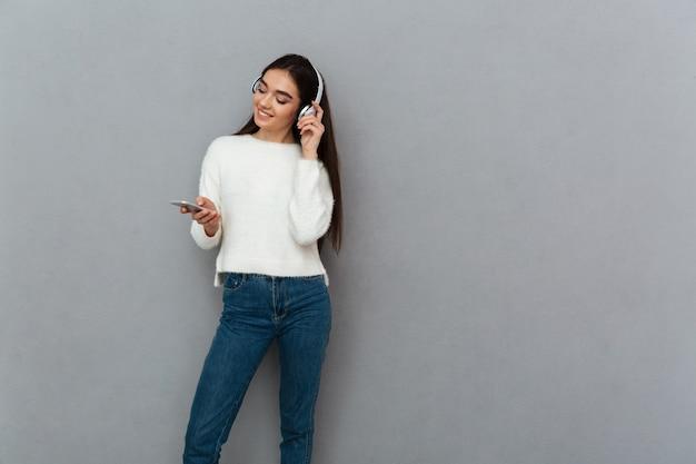 Donna sorridente del brunette nella musica d'ascolto delle cuffie e del maglione