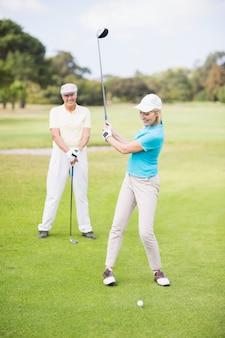 Donna sorridente del giocatore di golf che prende colpo