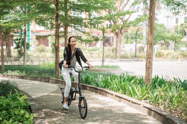 Donna sorridente di affari che guida la sua bici pieghevole