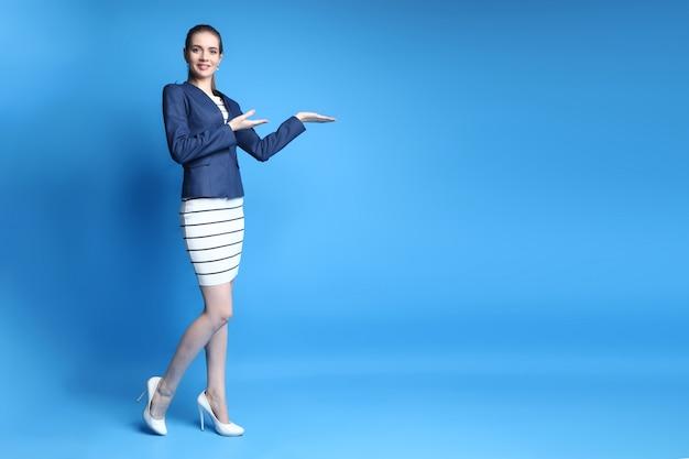 Donna sorridente di affari che indica allo spazio della copia su fondo blu