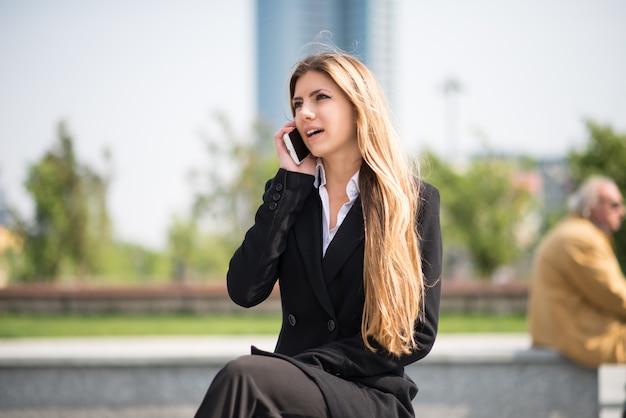 Donna sorridente di affari che per mezzo del suo telefono cellulare