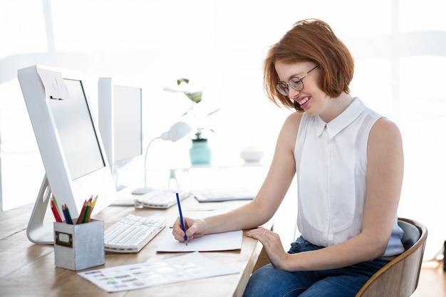 Donna sorridente di affari dei pantaloni a vita bassa che schizza sulla carta alla sua scrivania