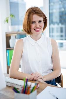 Donna sorridente di affari dei pantaloni a vita bassa che si siede nel suo ufficio con le sue mani sullo scrittorio