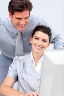 Donna sorridente di affari e il suo colleage che lavora ad un calcolatore