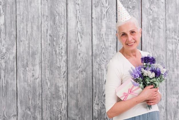 Donna sorridente di compleanno che tiene il mazzo del fiore e contenitore di regalo porpora davanti a fondo di legno grigio