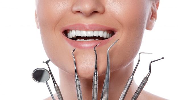 Donna sorridente e strumenti dentali
