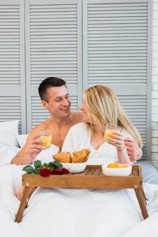 Donna sorridente e uomo con gli occhiali a letto vicino al cibo sul tavolo della colazione