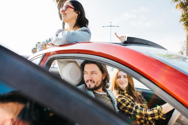 Donna sorridente ed uomo positivo che si siedono in automobile vicino a signora che si appoggia fuori dall'auto
