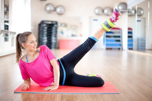 Donna sorridente fare esercizio con pesi gambe