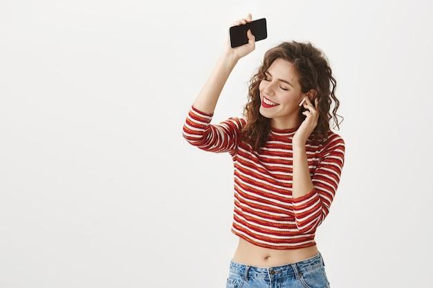 Donna sorridente felice ballando con lo smartphone in mano, ascoltando la musica in auricolari wireless