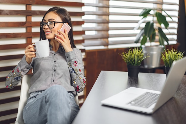 Donna sorridente felice che lavora con il computer portatile e che beve caffè