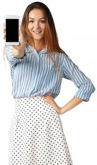 Donna sorridente felice che mostra telefono cellulare isolato nel bianco