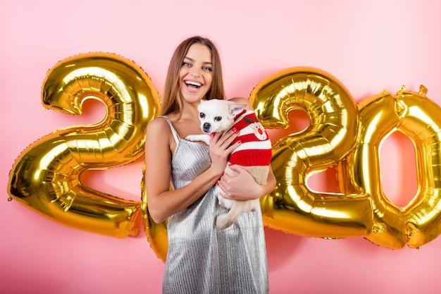 Donna sorridente felice con il cane bianco della chihuahua e palloni di natale 2020 isolati sopra il rosa