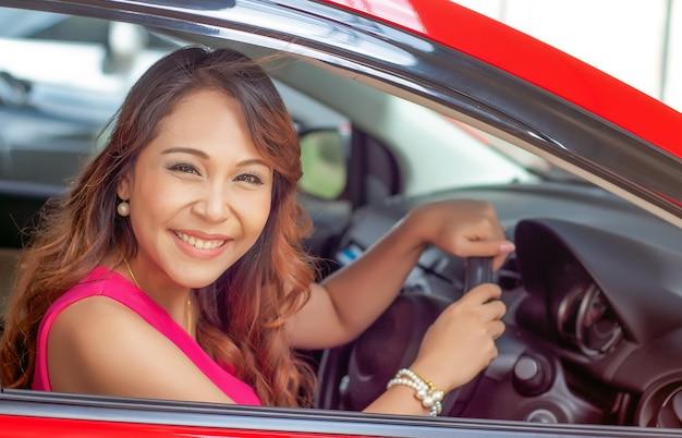 Donna sorridente felice con la chiave dell'automobile. guida