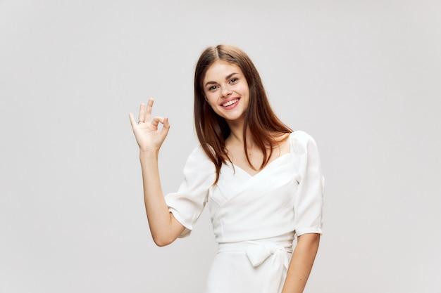 Donna sorridente gesticolando a un altro abito bianco studio ritagliata vista