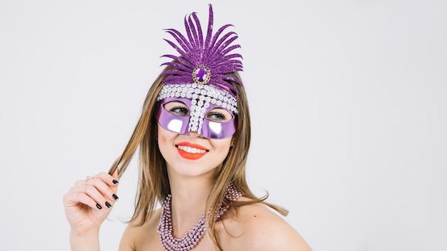 Donna sorridente graziosa che indossa la maschera decorativa porpora di carnevale su fondo bianco