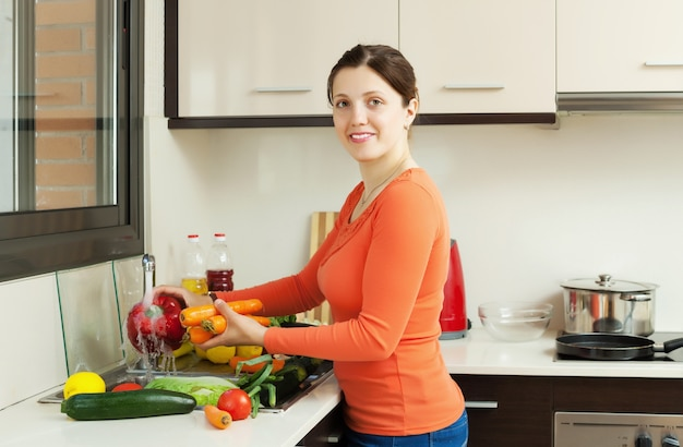 Donna sorridente graziosa che lavora le verdure fresche
