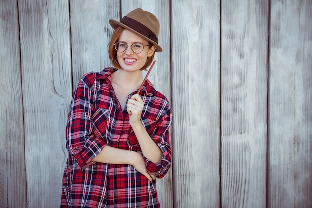 Donna sorridente hipster che tiene una matita,