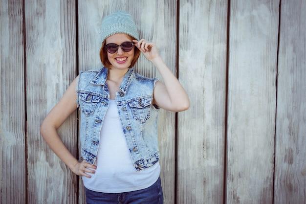 Donna sorridente hipster in occhiali da sole e un cappello a cuffia