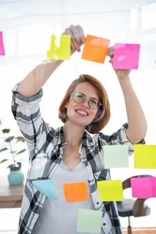 Donna sorridente hipster nel suo ufficio, attaccando le note a un muro